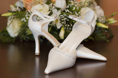 Brides shoes and flowers. Wedding bouquet and shoes. Sharpness is on the shoes Stock Photos