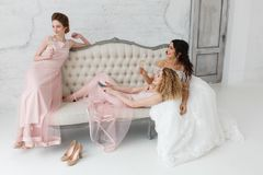 Brides talking and playing on sofa and drinking champagne. Morning preparation for wedding ceremony Royalty Free Stock Photography