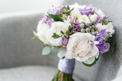 Brides wedding bouquet with peonies, freesia and other flowers on black arm chair. Light and lilac spring color. Morning. Brides wedding bouquet with peonies royalty free stock photos