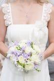 Brides wedding bouquet and wedding dress. Stock Photo