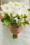 Brides wedding bouquet and wedding dress. Stock Photos