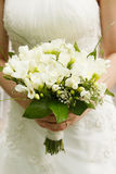 Brides wedding bouquet and wedding dress. Royalty Free Stock Images