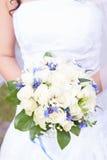 Brides wedding bouquet and wedding dress. Royalty Free Stock Photos