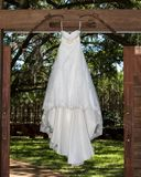 Brides wedding dress displayed hanging over doorway stock photo