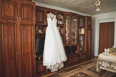The brides wedding dress hanging on a hanger in the room 9365. stock image