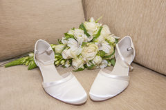 Brides wedding shoes with a bouquet Stock Photos
