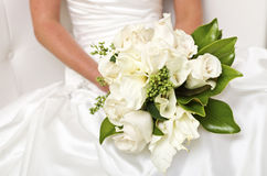 Brides White Floral Bouquet with Magnolia Leaves. Bride holds her white flower bouquet in her lap Stock Photography