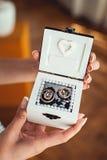 Bridesmade som rymmer en vit ask med vigselringar Arkivfoton