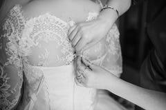 Bridesmaid в красных платьях помогает невесте к одетому платью свадьбы B Стоковое Изображение RF