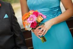 Bridesmaid и groomsman идя вниз с междурядья с красочным bo Стоковая Фотография