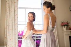 Bridesmaid регулируя платье свадьбы невесты в примерочной стоковая фотография
