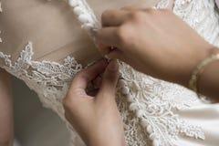 Bridesmaid шнурует белое платье свадьбы стоковые фотографии rf