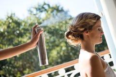 Bridesmaid applying hairspray to bride in dressing room Royalty Free Stock Image