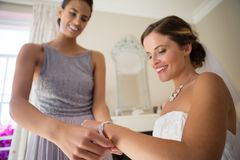 Bridesmaid assisting bride in getting dressed at fitting room Royalty Free Stock Image