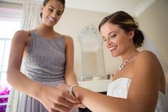 Bridesmaid assisting bride in getting dressed at fitting room. Smiling bridesmaid assisting bride in getting dressed at fitting room Royalty Free Stock Image