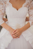 Bridesmaid buttoning the dress on bride. Details of beautiful wedding dress Royalty Free Stock Photo