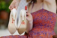 Bridesmaid displaying bride's shoes Stock Photos