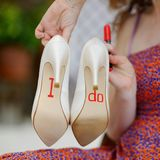 Bridesmaid displaying bride's shoes Stock Images