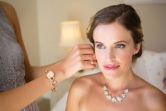 Bridesmaid dressing bride in fitting room Stock Images