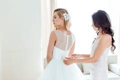 Bridesmaid dressing up bride Royalty Free Stock Photo