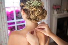 Bridesmaid fastening bride chain in dressing room Royalty Free Stock Photography