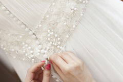Bridesmaid fixing bride's wedding dress Royalty Free Stock Photography