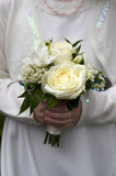 Bridesmaid or flowergirl holding a wedding bouquet. Flowergirl or bridesmaid holds bouquet of white roses Royalty Free Stock Image
