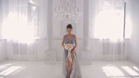 Bridesmaid in gray dress barefoot with bouquet goes directly to camera. We see large white hall draped with cloth, rays of sun through two open windows, two stock video footage