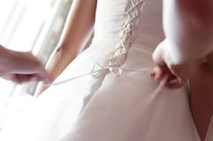 Bridesmaid helping bride fasten buttons on corset and getting her dress royalty free stock image
