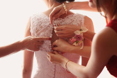 Bridesmaid helping bride geting her dress on Royalty Free Stock Image