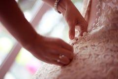 Bridesmaid helping bride tie her wedding dress Stock Photography