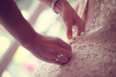 Bridesmaid helping bride tie her wedding dress Royalty Free Stock Photos