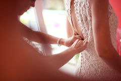 Bridesmaid helping bride tie her wedding dress Stock Image