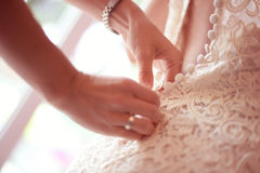 Bridesmaid helping bride tie her wedding dress Stock Images
