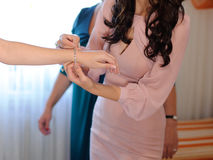Bridesmaid Helping Bride to Clasp Bracelet Stock Image