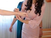 Bridesmaid Helping Bride to Clasp Bracelet Stock Image