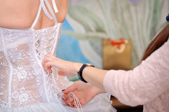 Bridesmaid is helping the bride to dress Royalty Free Stock Photos