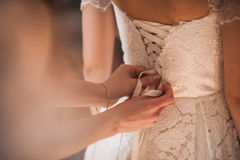 Bridesmaid helping the bride to dress Royalty Free Stock Image