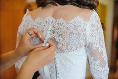 Bridesmaid is helping the bride to dress Royalty Free Stock Photo