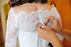 Bridesmaid is helping the bride to dress Royalty Free Stock Images