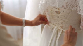 Bridesmaid is helping the bride to dress,close-up. Bridesmaid tying the corset on the wedding dress of the bride close-up stock footage