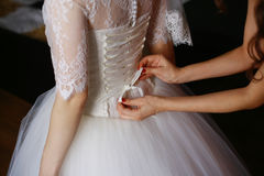 Bridesmaid is helping the bride to dress. royalty free stock images