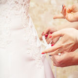 Bridesmaid is helping the bride to dress Royalty Free Stock Photography