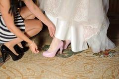 Bridesmaid Helping Bride Stock Photos
