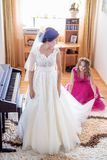 Beautiful young bride in wedding dress in living room Stock Photos