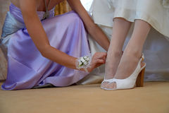 Bridesmaid helping bride to put on white shoes royalty free stock photo