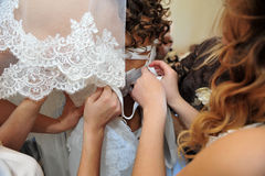 Bridesmaid is helping the bride tying bow on Royalty Free Stock Image