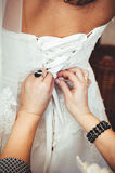 Bridesmaid is helping the bride tying bow on Stock Photography