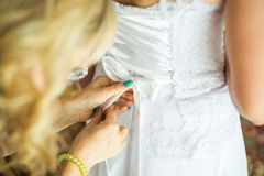 Bridesmaid helping the bride with the wedding dress Royalty Free Stock Image