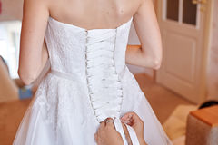 Bridesmaid helping to dress the bride in a wedding morning Stock Photography